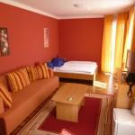 Zimmer mit Sitzecke, TV-Anrichte und Bett